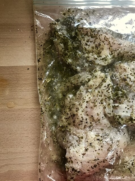 The Marinating bag, now sealed, laid down flat on the countertop. Breast pieces, oil and vinegar, and spices are all mixed together and evenly distributed around the chicken.