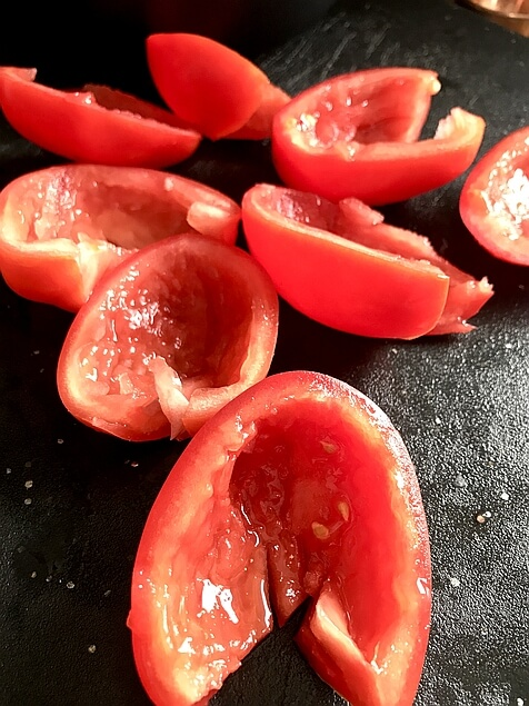 Picture shows eight delicious looking, freshly sliced Roma tomato halves. The liquid and seeds have all been scooped out.