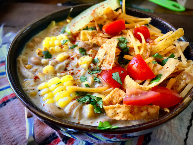Wow... my moth is watering uncontrollably! This picture of a hot, fresh bowl of this Instant Pot White Chicken Chili, garnished with tortilla strips, tomato, cilantro, cheese, and a slice of lime is both striking in its incredible mix of colors, and absolutely overpowering. But don't forget the greatest part- There's no willpower necessary... because IT'S SKINNYISH!