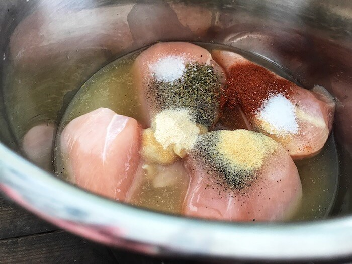 Raw chicken with spices and chicken broth in Instant Pot