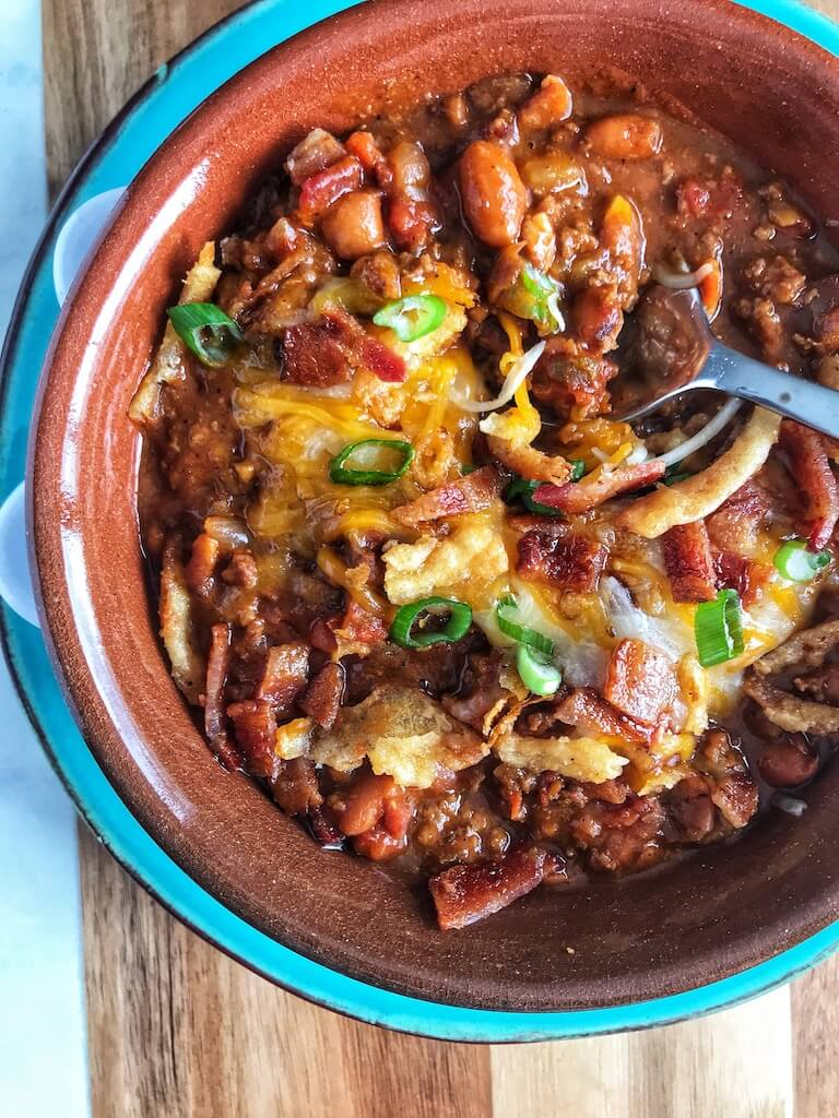 Bacon Cheeseburger Chili in a bowl with a spoon digging in