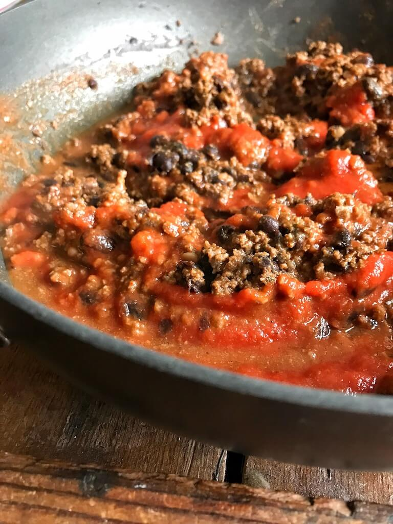 tomato sauce and water being added to the beef and bean taco meat