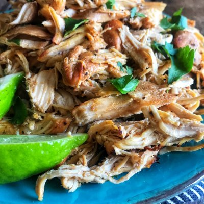 Slow Cooker Chicken Carnitas on a bright blue plate with a lime wedge