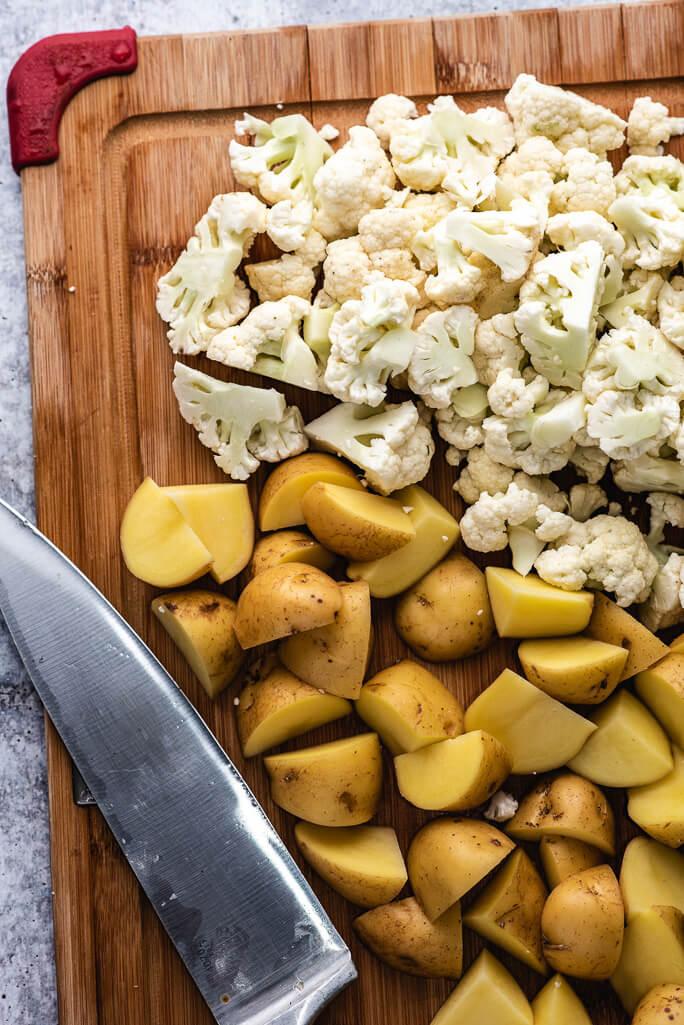 knife, potato chunks, cauliflower chunks on a cutting board