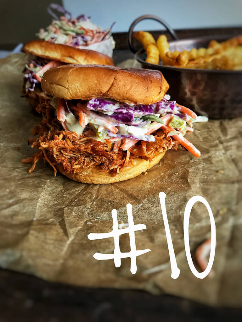SHREDDED BBQ WITH SLAW ON HAMBURGER BUN ON TOP OF CRUMBLED PARCHMENT PAPER WITH FRIES IN THE BACKGROUND