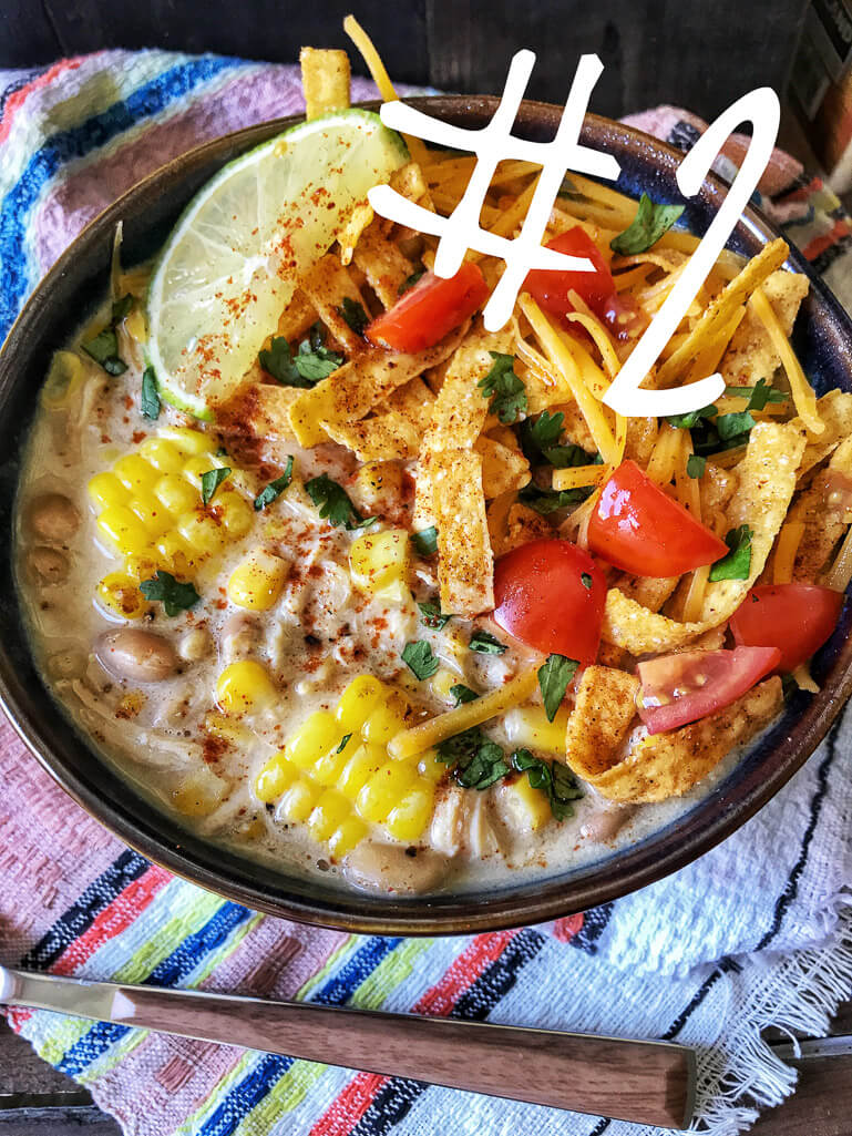 BOWL OF WHITE CHICKEN CHILI WITH TOMATOES, BROKEN TORTILLA CHIPS, AND TOMATO ON TOP