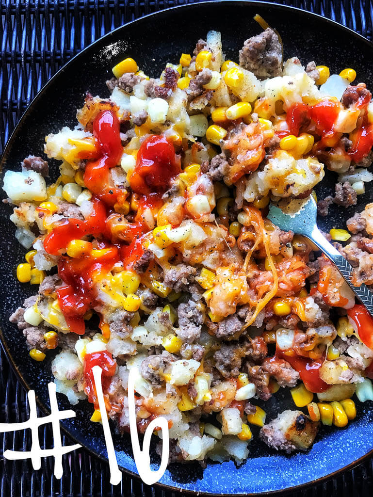 black plate with cooked ground beef, corn, potatoes, shredded cheese, and ketchup with a fork