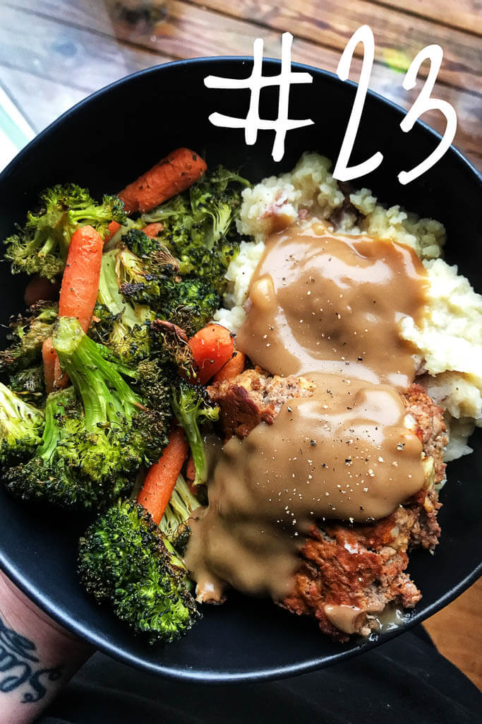 black bowl with meatloaf and gravy, carrots and broccoli, and pile of mashed potatoes