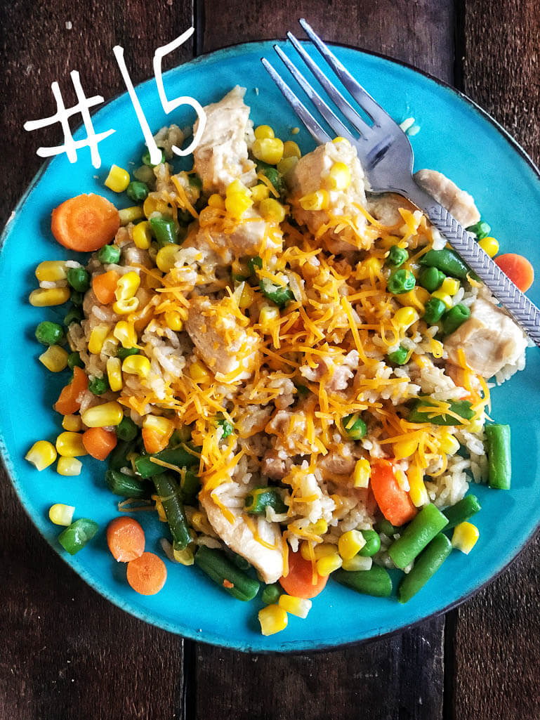 chicken and rice with cheese and corn, carrots, green beans on a bright blue plate with a fork