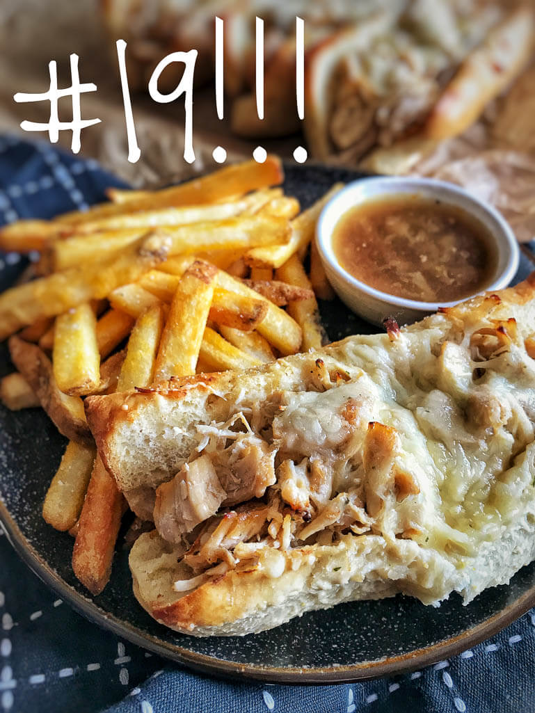 roll with chopped chicken covered in mozzarella cheese, small cup of au jus, and golden french fries on the side