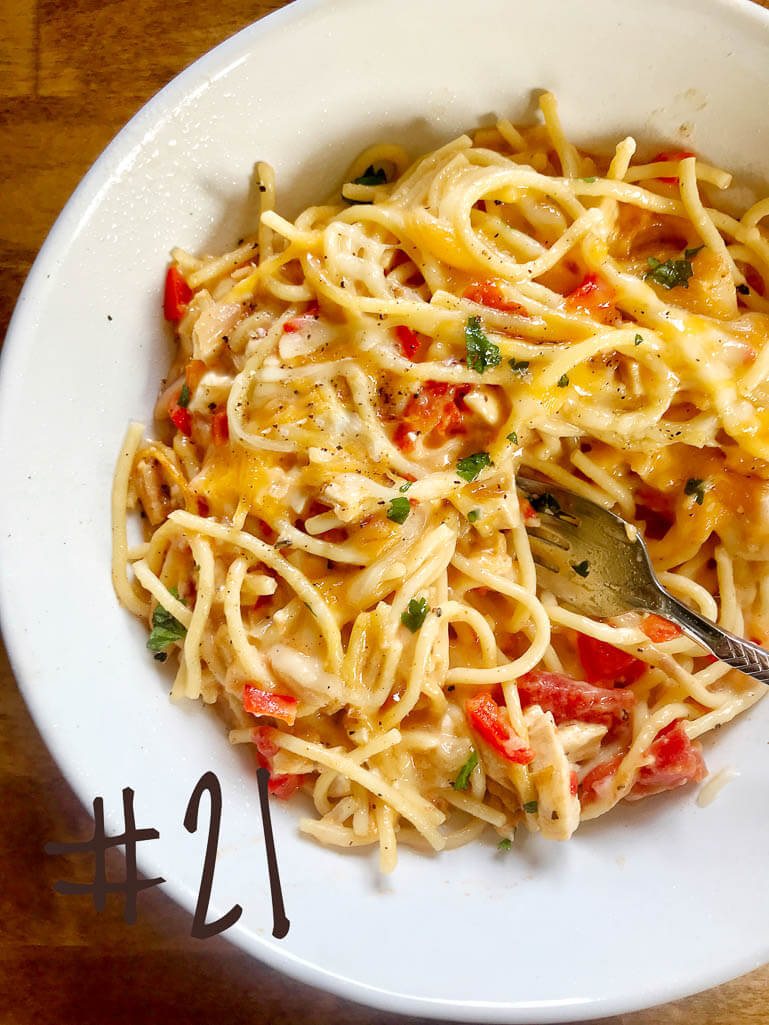 cheesy chicken spaghetti white bowl with  spaghetti noodles, tomatoes, chicken, cheese, red peppers, and cilantro