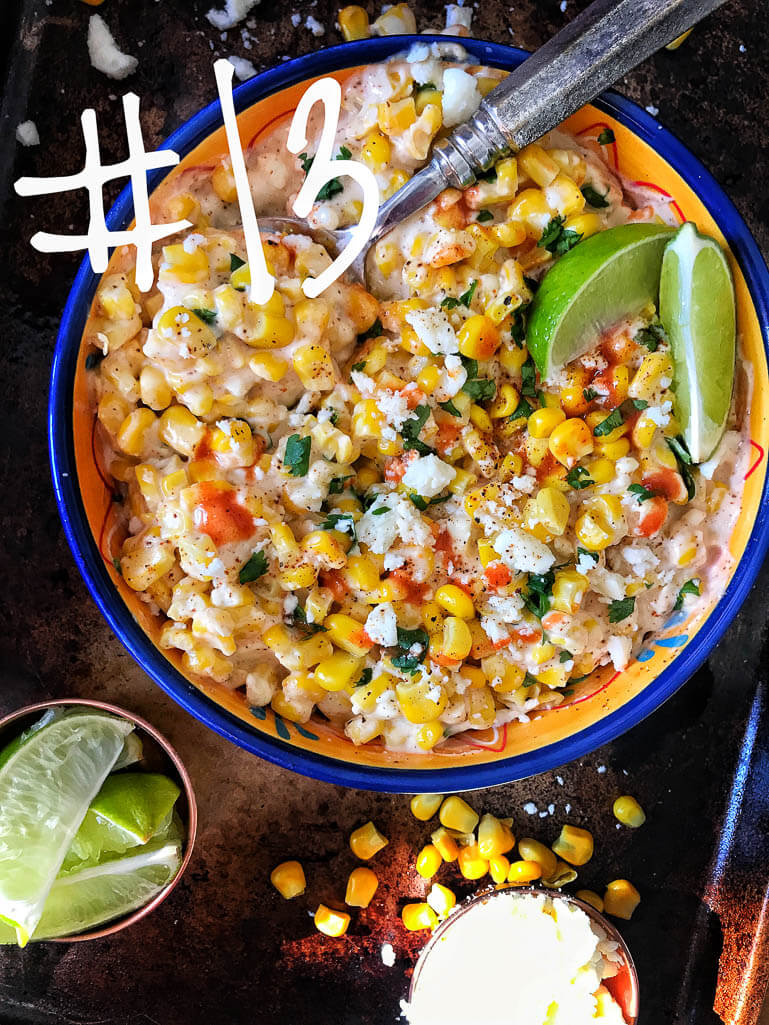 corn in a bowl with limes, cilantro, and mayo