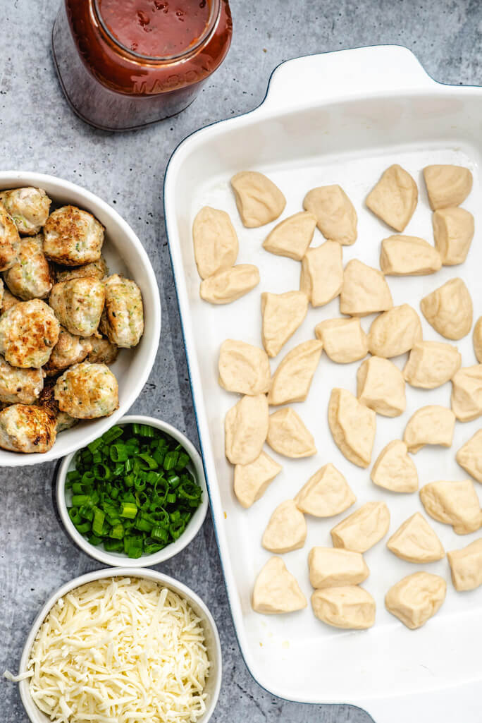9x13 casserole dish filled with biscuit pieces and a bowl of green onions and meatballs on the side