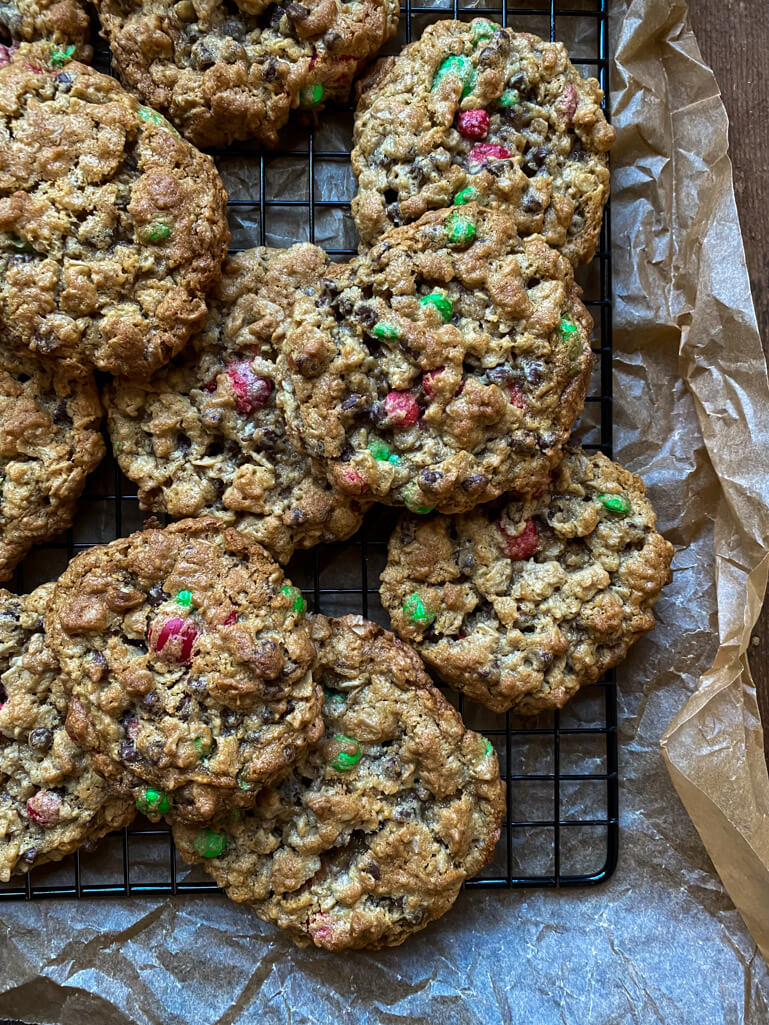 monster cookies with red and green m&ms on a cooling rack and parchment paper