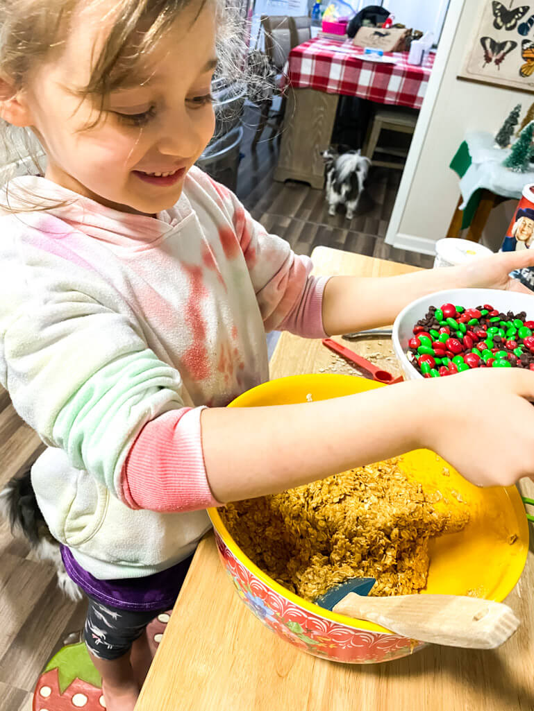 Pepper with m&ms pouring into a yellow bowl