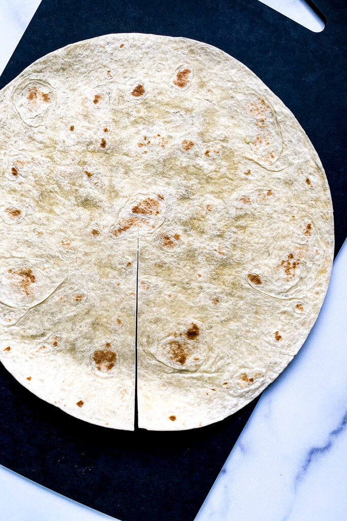 large tortilla, cut in the middle, on a black cutting board