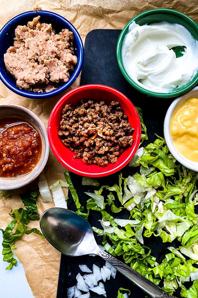Ingredients: shredded lettuce, spoon, bowls of seasoned ground beef, salsa, refried beans, greek yogurt, cheddar cheese