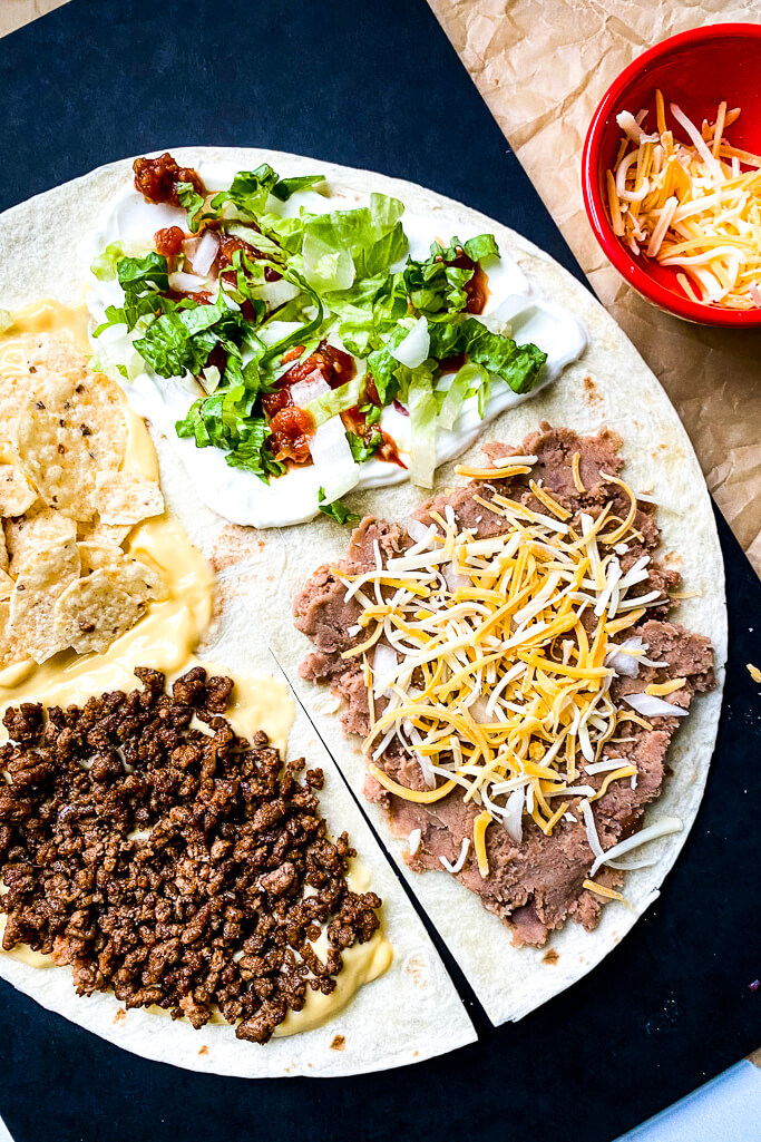 burrito shell with four quadrants: nacho cheese, beef,  crushed tortilla chips, refried beans, shredded cheese, sour cream, lettuce, and tomatoes