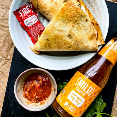 taco crunchwrap with salsa and bottle of taco sauce