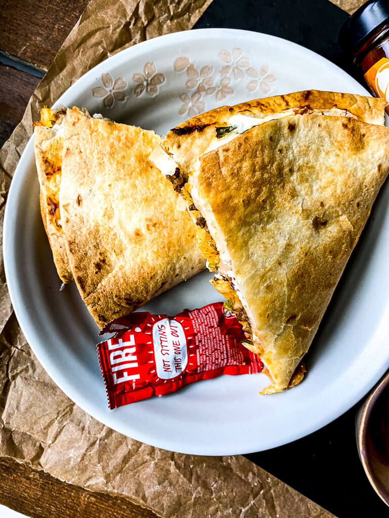 taco crunchwrap on a plate with a taco sauce packet