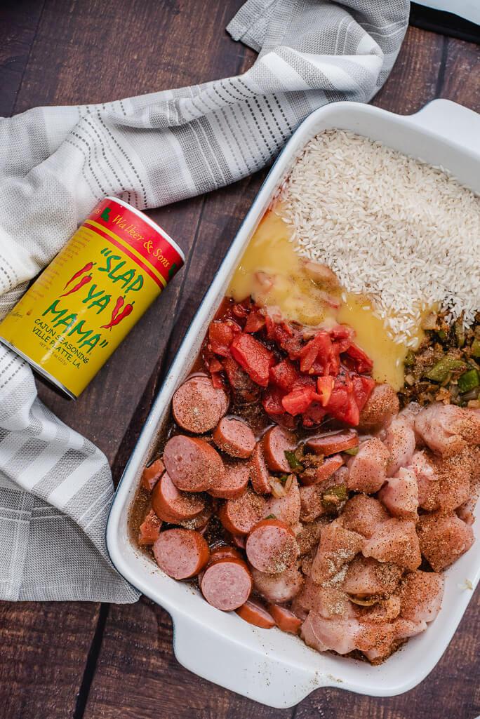 raw rice, sausage, diced tomatoes, slap ya mama seasoning, chicken in a casserole dish