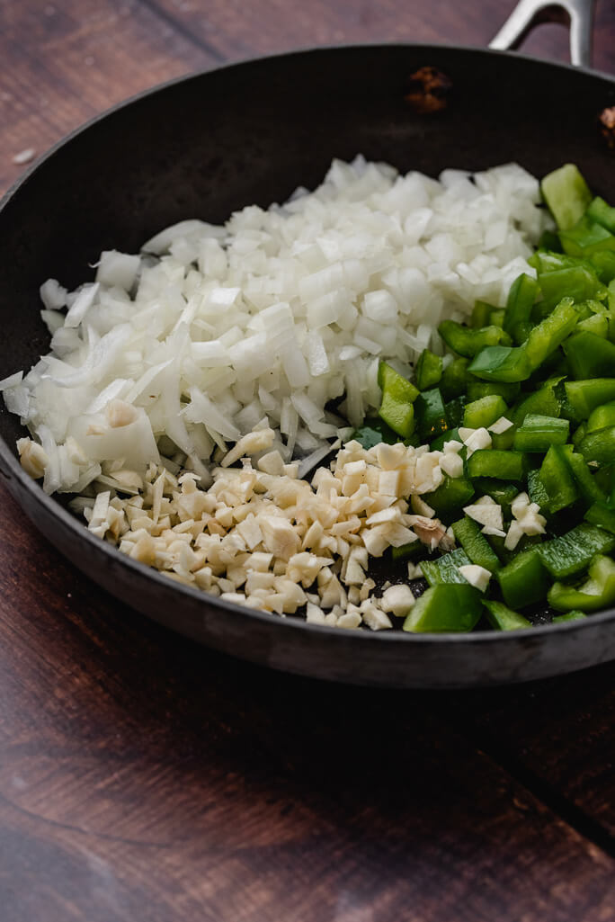 chopped up green pepper, onion, and garlic in a skillet