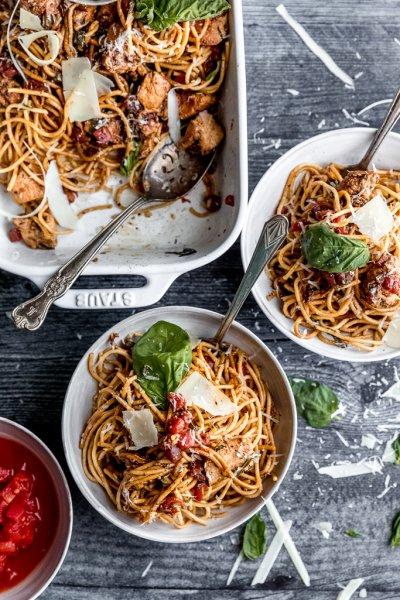 two bowls of bruschetta chicken spaghetti with basil
